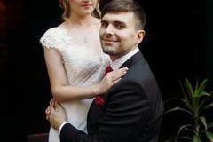 Schöne romantische Jungvermähltenpaare, die nahe Blumenblumensträußen umarmen Lizenzfreies Stockbild