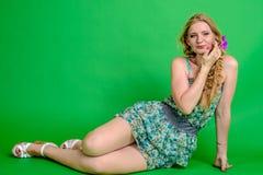 Schöne romantische Mädchenblondine im Sommerkleid mit Orchideenblume Lizenzfreie Stockfotografie