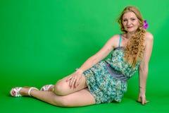 Schöne romantische Mädchenblondine im Sommerkleid mit Orchideenblume Lizenzfreie Stockfotos