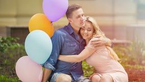 Schöne romantische Paare, die den Jahrestag, umarmend auf Bank im Park feiern stockfoto