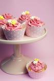 Schöne rosa kleine Kuchen in den Sternhaltern auf rosa Kuchen stehen Stockfotografie