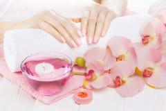 Schöne rosa Maniküre mit Orchidee, Kerze und Tuch auf dem weißen Holztisch stockfoto