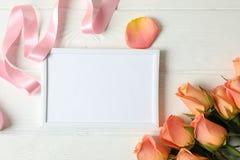 Schöne rosa Rosen, Band und leerer Rahmen auf hölzernem Hintergrund lizenzfreie stockfotos
