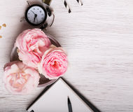 Schöne rosa Rosen und Uhr auf weißer Tabelle Stockfotos