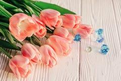Schöne rosa Tulpen mit blauen Edelsteinen auf weißem rustikalem hölzernem Stockfotografie