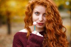 Schöne rote behaarte Frau mit Süßigkeit in der Hand, Intrige stockfoto