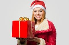 Schöne rote Haarfrau, die ein großes Weihnachtsgeschenk hält Stockfotos