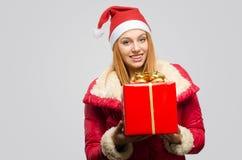 Schöne rote Haarfrau, die ein großes Weihnachtsgeschenk hält Stockfoto