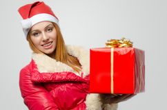 Schöne rote Haarfrau, die ein großes Weihnachtsgeschenk hält Stockbild