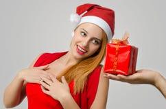 Schöne rote Haarfrau, die ein Weihnachtsgeschenk empfängt Stockbild