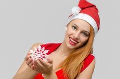 Schöne rote Haarfrau, die eine Schneeflocke hält Lizenzfreies Stockfoto