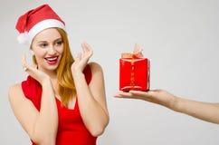 Schöne rote Haarfrau regte das Empfangen eines Weihnachtsgeschenks auf Stockfotografie