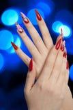 Schöne rote Nägel und blaue Leuchten Lizenzfreie Stockbilder