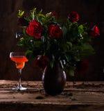 Schöne rote Rosen im Vase und im Glas Wein Lizenzfreies Stockfoto