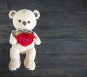 Schöne rote Rosen und rotes Herz auf hölzernem Hintergrund Lizenzfreie Stockfotos