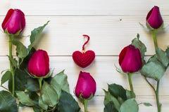 Schöne rote Rosen und rotes Herz auf hölzernem Hintergrund Stockfotos