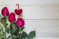 Schöne rote Rosen und rotes Herz auf hölzernem Hintergrund Stockfoto