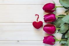 Schöne rote Rosen und rotes Herz auf hölzernem Hintergrund Stockfotografie