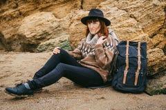 Schöne rothaarige Frau in einem Hut und in einem Schal mit einem Rucksack sitzt auf der Küste auf dem Hintergrund der Felsen lizenzfreies stockbild