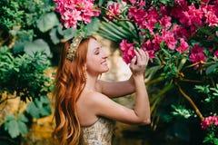 Schöne rothaarige Frau inhaliert Geruch von blühenden Blumen stockfoto