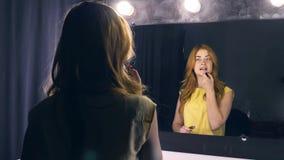 Schöne Rothaarigefrauen, die Make-up nahe Spiegel anwenden stock footage