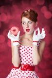 Schöne Rothaarigefrauen mit Donut. Stockbilder