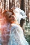 Schöne Rothaarigefrauen-Waldnymphe in einem blauen transparenten hellen Kleid im Wald, das in Tanz spinnt Rote Haarmädchen Kunstm lizenzfreie stockfotos