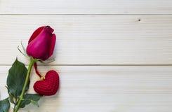 Schöne Rotrose und rotes Herz auf hölzernem Hintergrund Stockfotos