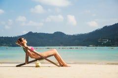 Schöne, ruhige bräunende Dame beim Lügen im Aufenthaltsraum mit einem Fruchtcocktail auf dem Strand Stockbild