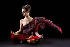 Schöne ruhige Frau meditiert in Lotussitz Stockbild