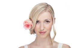 Schöne ruhige Frau mit einer Rose in ihrem Haar Lizenzfreies Stockfoto