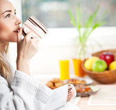 Schöne ruhige junge Frau, die Morgenkaffee trinkt Stockbilder