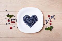 Schöne saftige reife natürliche organische Himbeerbrombeerblaubeeren und tadellose blaue Tischdecke punktiert weißes Tellerherz-F Stockfotos