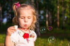 Schöne Schlagseifenblasen des kleinen Mädchens Lizenzfreie Stockfotos