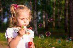 Schöne Schlagseifenblasen des kleinen Mädchens Stockfotos
