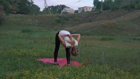 Schöne schlanke Frau, die morgens Yoga Asanas im Stadt-Park tut stock video