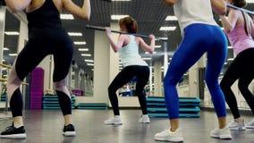 Sch?ne schlanke junge Frauen hocken mit einem Barbell stock video footage