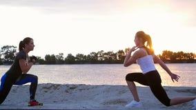 Schöne, schlanke junge Frauen nehmen an Eignung, springen, durchführen Stärkeübungen teil An der Dämmerung am sandigen Steinbruch stock footage