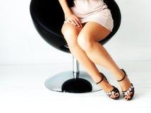 Schöne schlanke weibliche Beine in den Fersen auf einem weißen Hintergrund Lizenzfreie Stockbilder