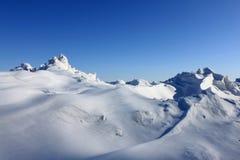 Schöne Schneewehe gegen den blauen Himmel Lizenzfreie Stockfotos