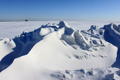 Schöne Schneewehe gegen den blauen Himmel Stockbild