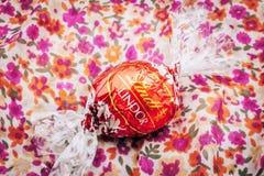 Schöne Schokoladentrüffel Lindt Lindor auf einer roten Luxusseide Lizenzfreies Stockbild