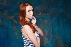 Schöne schoolmiss mit dem roten Haar in gestreiftem T-Shirt Stockfotografie