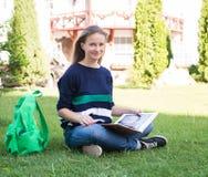 Schöne Schule oder Studentin, die auf dem Gras mit Büchern sitzen und Tasche studierend in einem Park stockfotos