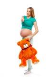 Schöne schwangere blonde Frau in den Pyjamas, die einen Spielzeugbären halten und darstellen, greift herauf alle sich fehlt gut a Stockbilder