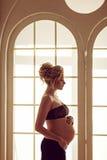 Schöne schwangere Blondine in einem schwarzen Rock und in einem Spitzenoberteil hält Th lizenzfreies stockbild