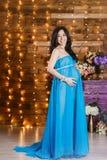 Schöne schwangere Brunettefrau im langen silk blauen Kleid stockfoto