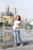 Schöne schwangere Frau auf dem Weg im Freien auf dem Stadtplatz nahe den Brunnen Frau, die im Park sich entspannt Lizenzfreies Stockbild