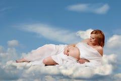 Schöne schwangere Frau auf den Wolken. Lizenzfreies Stockbild
