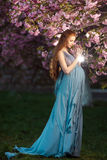 Schöne schwangere Frau in blühendem Garten Lizenzfreies Stockbild